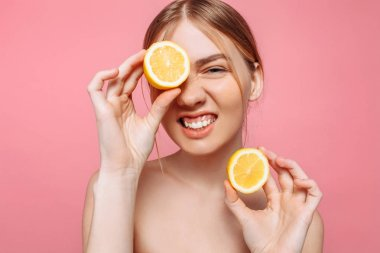 Portrait of a cheerful feminine girl, natural clear skin, a girl with two pieces of lemon, covering one eye with a lemon, isolated on a pink background. Skin care concept, natural beauty