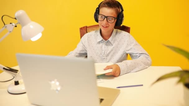 Happy teen guy in headphones using a laptop computer, learning through an online e-learning system, on a yellow background