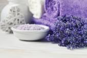 Fotografia Fiori di lavanda, sale marino aromatico e asciugamani. Concetto per il salone di spa, bellezza e salute, negozio di cosmetici. Chiuda sulla foto su fondo di legno bianco