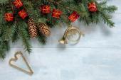 Vánoční pozadí s větve stromů jedle, kužely, zlatá trumpeta a vánoční srdce tvar ozdoby. Vánoce a nový rok koncept. Detail, horní pohled na světle modré dřevěný stůl, místo pro váš text