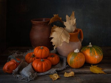 autumn still life with pumpkins and autumn leaves in ceramic jug on wooden background