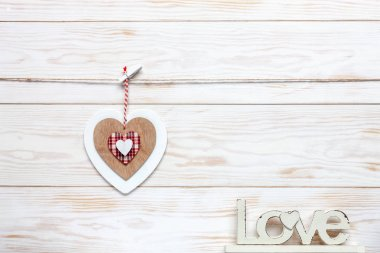 Wooden colorful heart on rope. Concept for Valentine's Day, wedding, engagement and other romantic events. Top view, close-up, flat lay on white wooden background