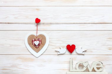 Wooden heart on rope, letters Love and figurines of pigeons