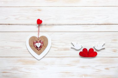 Wooden heart on rope and figurines of pigeons with hearts. Concept for Valentine's Day, wedding, engagement and other romantic events. Top view, close-up, flat lay on white wooden background