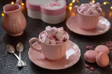Two pink cups with pink heart-shaped marshmallows, a gift in a pink box and pink macarons. Romantic breakfast for two. Close-up, selective focus.