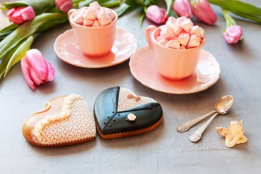 Two pink cups with pink heart shaped marshmallows, pink tulips