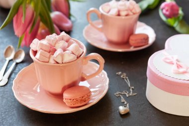 Two pink cups with pink heart shaped marshmallows with macaroons, pink tulips,  gift box and silver heart shape pendant on chain. Romantic breakfast for two. Close-up, selective focus.