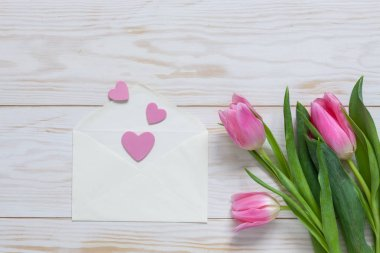 Bouquet  of pink tulips and hearts pattern in paper envelope. Top view, close-up, flat lay on white wooden background