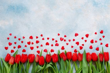 Bouquet  of red tulips and red heart figurines. Concept for Valentine's Day, womens day and other romantic events. Top view, close-up, flat lay