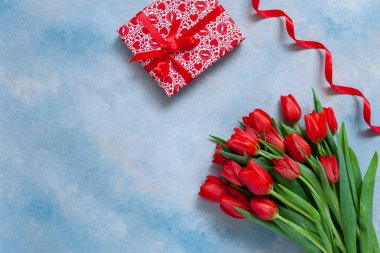 Bouquet  of red tulips and gift box with red ribbon. Concept for Valentine's Day, womens day and other romantic events. Top view, close-up, flat lay