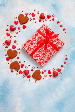 Wreath of sweets, cookies and heart figurines with gift box on  blue background. Concept for Valentine's Day, March 8th and other romantic holidays and events