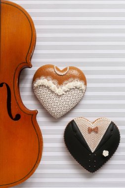 Old violin and two gingerbread heart shape figurines. Bride and groom. Top view, close up, flat lay on white music paper  background
