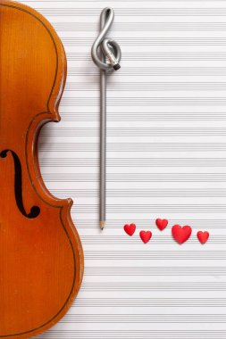 Old violin, pencil treble clef shape and red heart figurines. Top view, close up, flat lay on white music paper background
