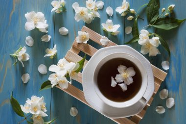 A cup of  tea on wooden mini pallet surrounded by jasmine flower