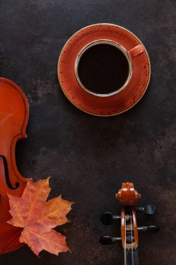 Two old violins with cup of hot coffee and autumn maple leaf on dark background