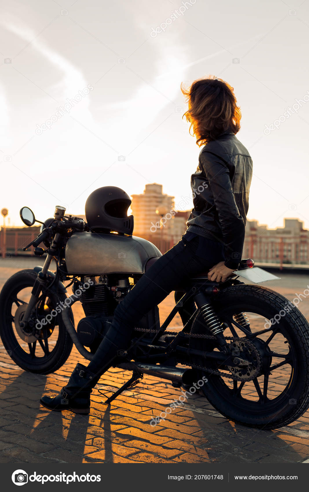 b04eb1f93c33d Femme sexy biker en blouson de cuir noir assis sur la moto vintage  caferacer personnalisé et toucher des lunettes de soleil. Parking toit  urbain, coucher de ...