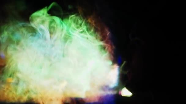 A férfi dohányzik a vízipipa, felszabadító egy slukk füst a szájából. Világító füst a fekete háttér