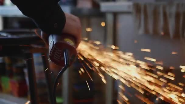The master cuts a metal product with an angle grinder. In workshop
