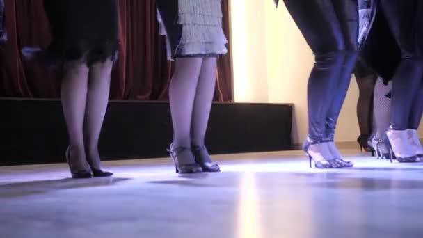 Tančící dívky ve starožitním klubu. V rámu pouze nohy.