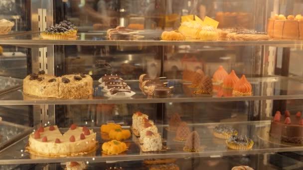 Üvegpult változatos színes süteményekkel és desszertekkel
