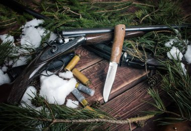 Hunting still life with a knife and two rifles.
