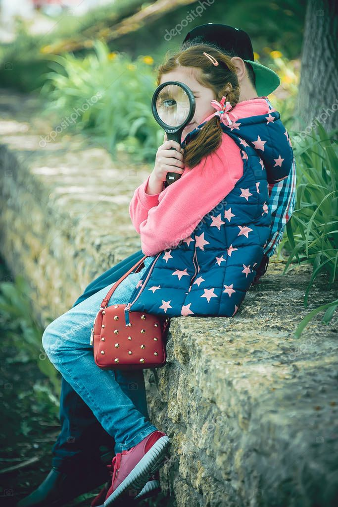 girl playing with magnifying glass, in the park, sitting on the fence in summer