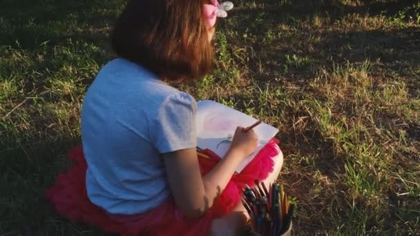 girl painter paints a flower while sitting on her lap, on the grass in a warm summer park
