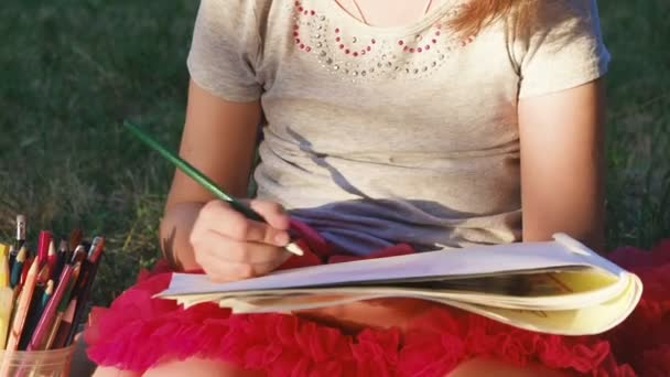 girl in a red skirt, in the album draws pictures with pencils, on the nature in the park