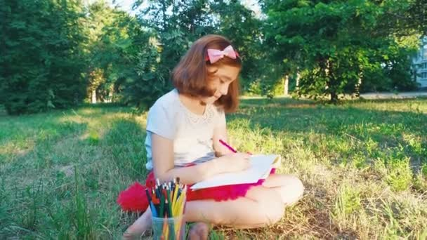 girl in a red skirt, in an album draws pictures with pencils, outdoors in a park, sitting on the grass