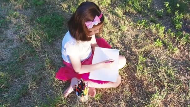 little artist girl in a red skirt draws with pencils in the album, sitting on the grass, in a forest park, top view