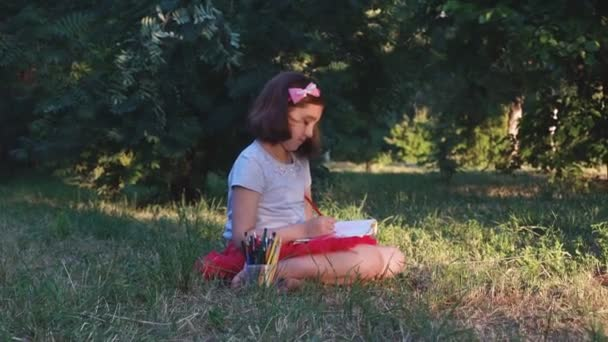 little artist girl in a red skirt draws a picture with pencils in the album, sitting on the grass, in a forest park