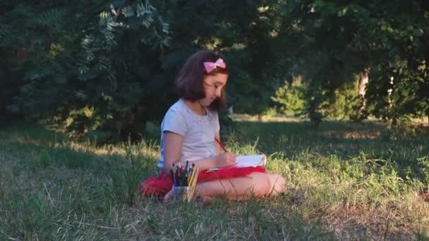 egy piros szoknya, kislány művész felhívja a kép ceruzák az album, ül a fűben, egy erdei Park