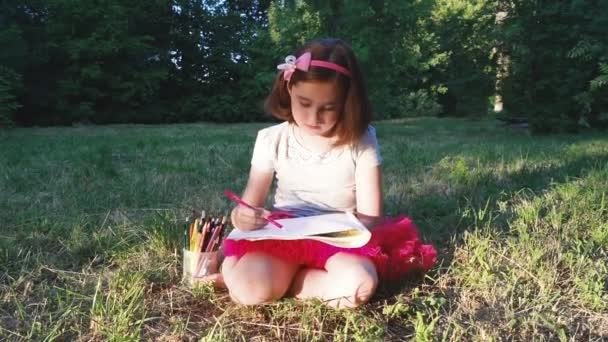 little girl in a red skirt draws in an album with pencils in a park in nature, sits on the grass