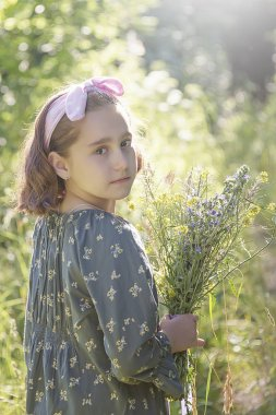 little girl with a bouquet of wildflowers, walk through the forest on the edge of a portrait