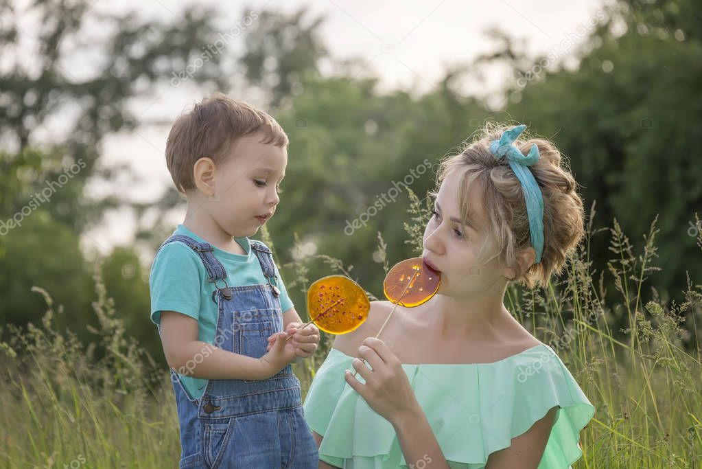 Mom and son in the park in the summer with lollipops and soap bubbles