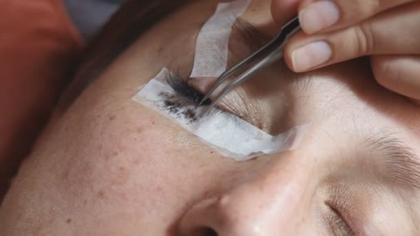 eyelash extension at home, the girl performs an operation at home