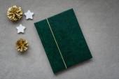 Karácsonyi kompozíció, zöld notebook, fehér csillag és arany fenyő kúpok a világos háttér, karácsonyi hangulat. Szemközti nézet.