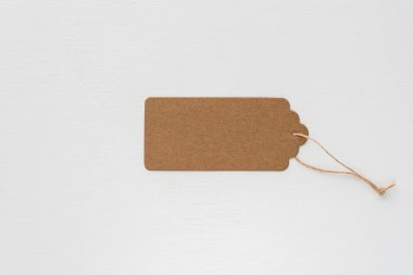 Blank paper tag with rope on white background, isolate. Recycled cardboard tag. Price tag for discounts, gift tag, sale tag.