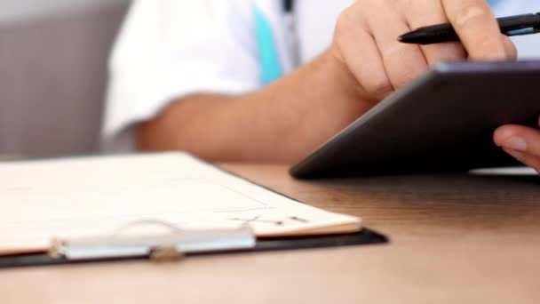 Medical doctor working with tablet computer and writting prescription