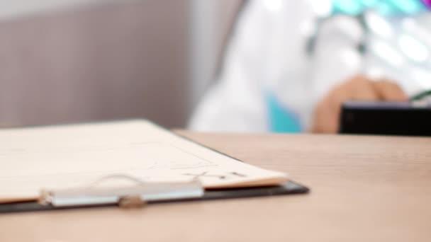 Arzt arbeitet mit Tablet-Computer und schreibt Rezept