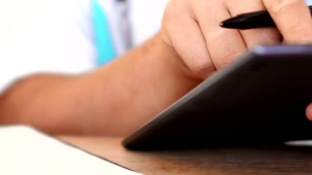 Arzt arbeitet mit Tablet-Computer und Schreiben Rezept