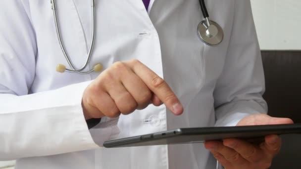 Male doctors hands using his modern digital tablet computer.