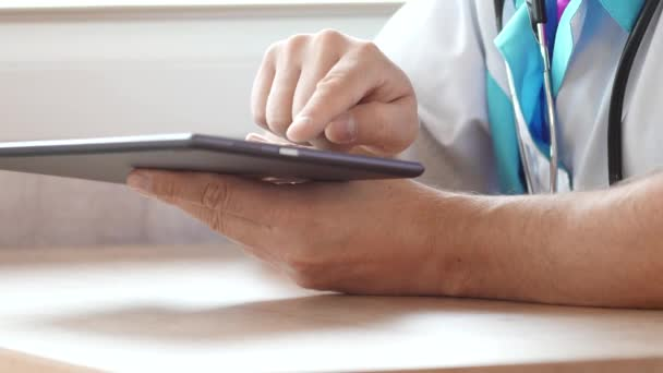 Male doctor working with a modern touchscreen tablet computer