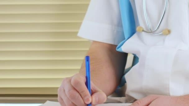 Männlichen Arzt Arzt schreiben Rx Rezept in Zwischenablage für seine Patienten