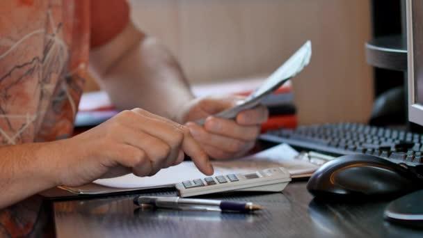 Člověk počítá peníze a vyplnění daňového formuláře