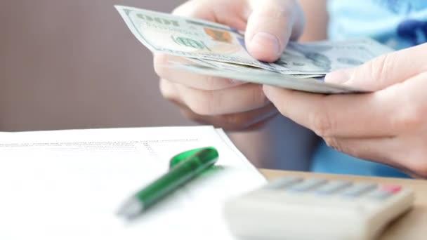 Muž počítání dolarů a vyplnění daňového formuláře. Výpočet nákladů a psaní na daňovém dokladu