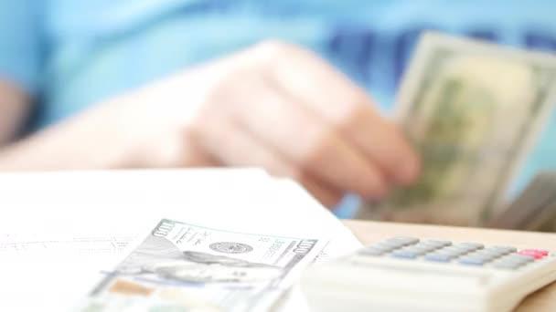 Uomo contando dollari e riempiendo il modulo fiscale. Egli spese di calcolo e scrivendo sul documento fiscale