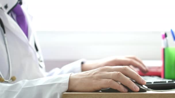 Medical doctor working on laptop in his cabinet and clicking computer mouse.