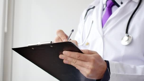 Closeup of male doctor hand writing a medical prescription.