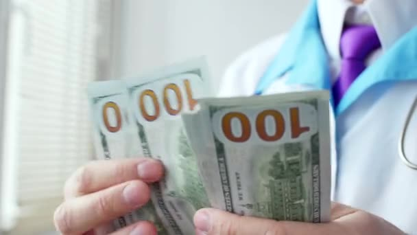 Male medical doctor counting hundred dollars banknotes